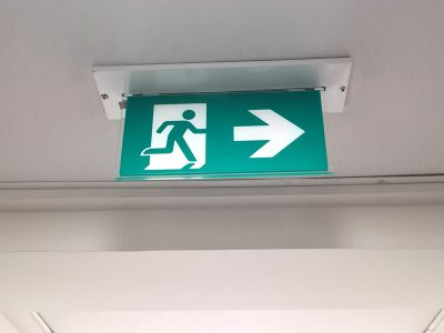 green exit sign at the ceiling in the narrow hall with regular ceiling lights white walls