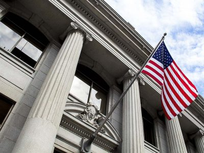 American flag flying over government building in city, blue sky and clouds