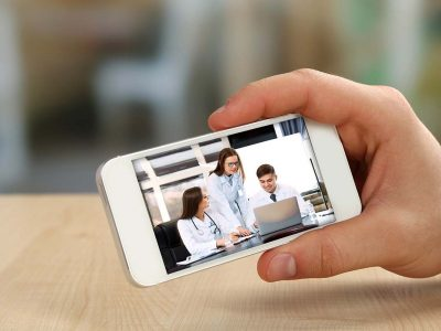 Hand holding mobile device viewing a group of healthcare professionals in a meeting.