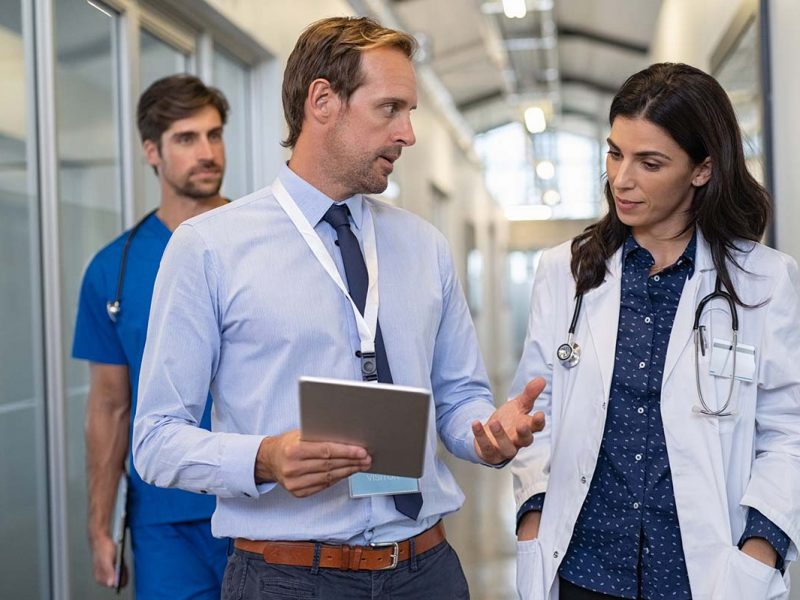 Man and woman doctor having a discussion in hospital hallway while holding digital tablet. Doctor discussing patient case status with his medical staff after operation. Pharmaceutical representative showing medical report.