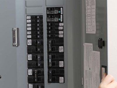 Close up woman checking electricity distribution box
