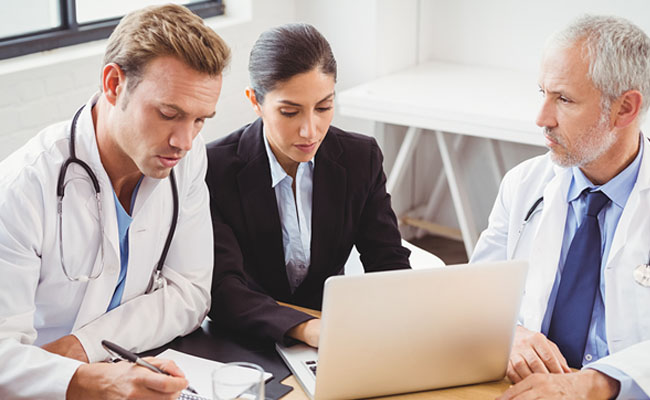 Medical team using laptop in conference room in hospital