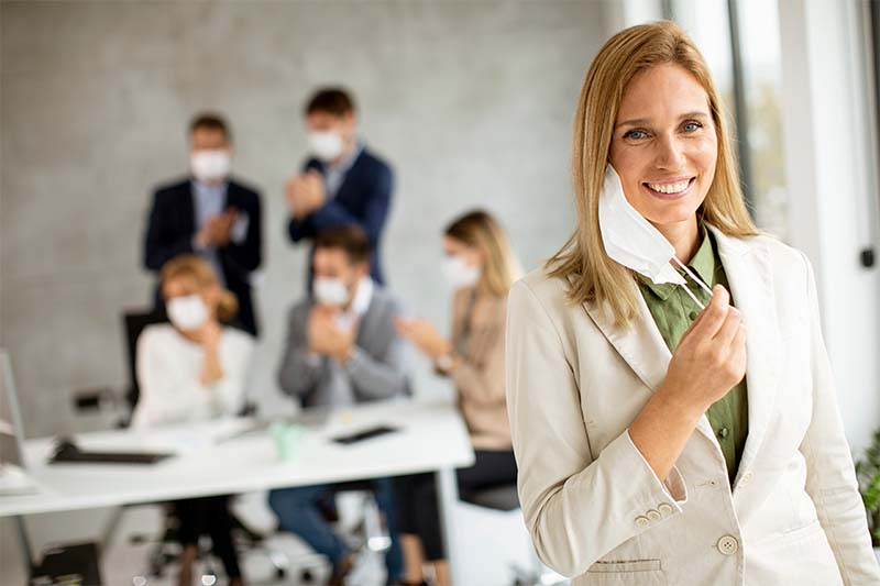 Attractive Business Woman Taking Off Her Protective Facial Mask