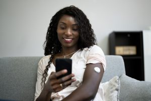 African,Woman,Using,Continuous,Glucose,Remote,Monitor,Diabetes,Sensor