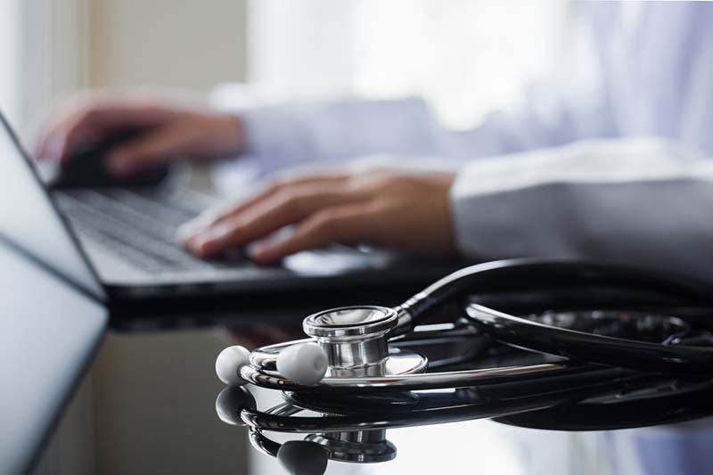 Female doctor in white lab coat typing on laptop computer with notebook and medical stethoscope on the desk at workplace. Medical technology ,Electronic health record system (EMR) concept