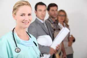 Female,Nurse,Stood,Next,To,Four,Professionals,From,Different,Backgrounds