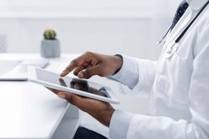 Technologies in medical field. Cropped of black doctor using digital tablet at workplace