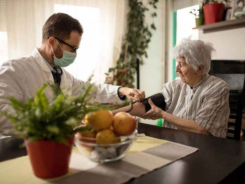 Young serious Caucasian doctor wearing face mask adjusting blood pressure gauge on senior gray-haired woman's hand during house call medical check-up
