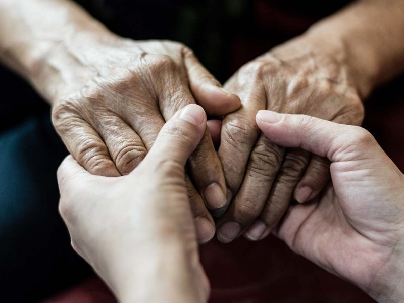 Elderly person and young person holding hands