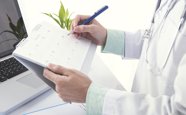 Doctor hand marked appointment for patient on calendar. concept planner health care.