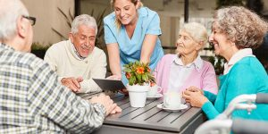 Caregiver with tablet pc and a group of seniors in retirement home