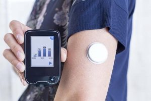 closeup of a hand of a young woman showing a reader after scanning the sensor of the glucose monitoring system beside the sensor placed on her arm - focus on the reader