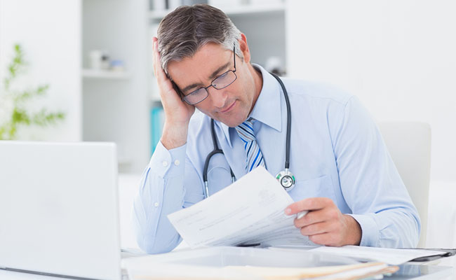 Tensed male doctor reading document at table in clinic